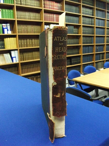 "Damaged spine of ""Atlas of head sections"" by William Macewen"